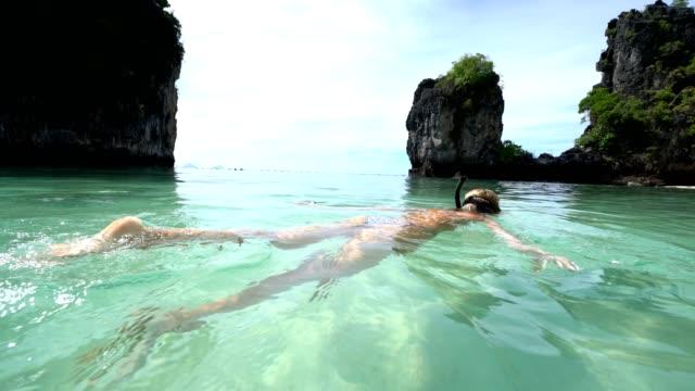 stockvideo's en b-roll-footage met een vrouw snorkelen in het warme turquoise water van thailand - baai