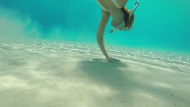 ms woman snorkeling underwater,grabbing handful of sand - хорватия стоковые видео и кадры b-roll