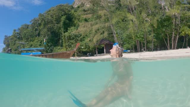 Woman snorkelling in tropical waters. Half in half out shot. Woman snorkelling in tropical waters. Half in half out shot. aqualung diving equipment stock videos & royalty-free footage