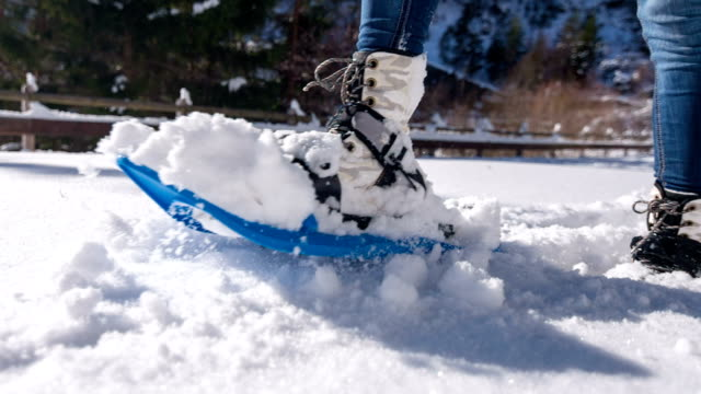Woman snowshoeing on fresh snow Female spending her free time snowshoeing on freshly fallen snow in the mountainside stepping stock videos & royalty-free footage