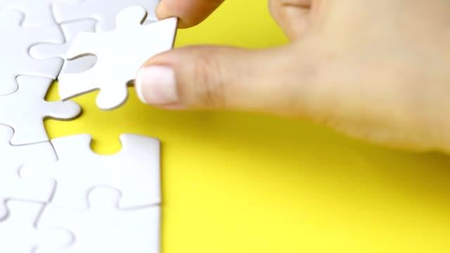 donna che risolve un puzzle impegnativo aggiungendo l'ultimo pezzo - concetti e temi video stock e b–roll