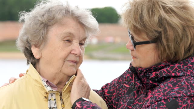 Mujer calma a vieja durante el estrés al aire libre - vídeo