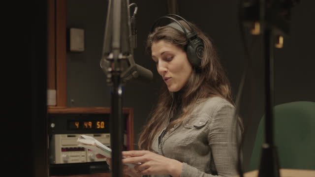 vidéos et rushes de une femme s'exprimant dans un studio de radio - podcasting