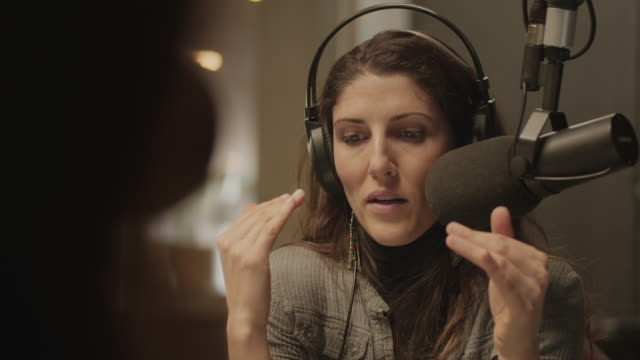 vidéos et rushes de une femme parlant avec quelqu'un dans un studio de radio - podcasting