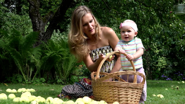 woman spend freetime with baby daughter in park with apple. FullHD video