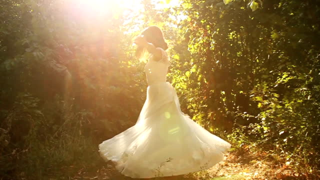 woman spinning dress slow motion nature sun forest happiness - wedding fashion stock videos and b-roll footage