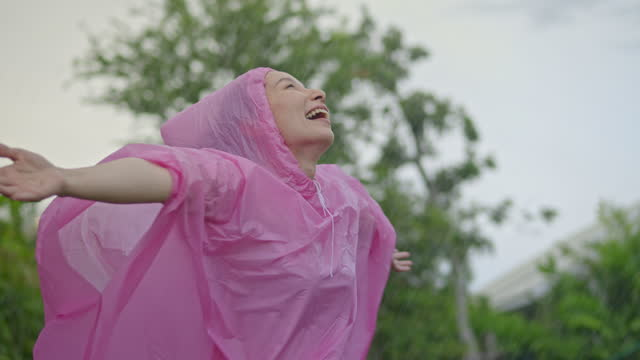 SLO MO Woman spinning in summer rain
