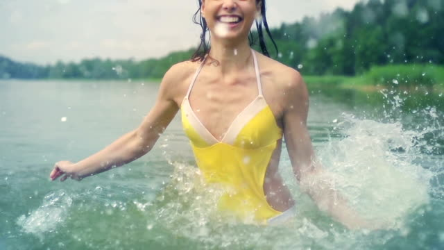 woman splashing water Young woman having fun splashing water at camera. Slow motion. swimwear stock videos & royalty-free footage