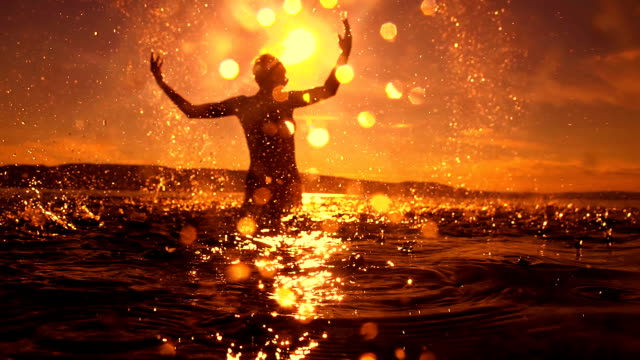 HD SUPER SLOW MO: Woman Splashing Water HD1080p: SUPER SLOW MOTION shot of of silhouette of a young woman splashing water over herself while standing in shallow water in the sea at sunset. silhouette people stock videos & royalty-free footage
