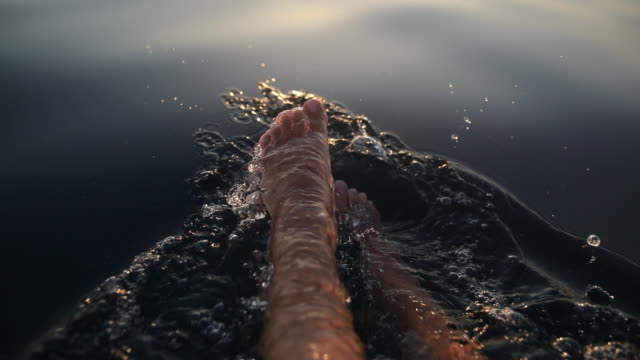 Woman splashing water with her legs in sea during sunset on summer vacation video