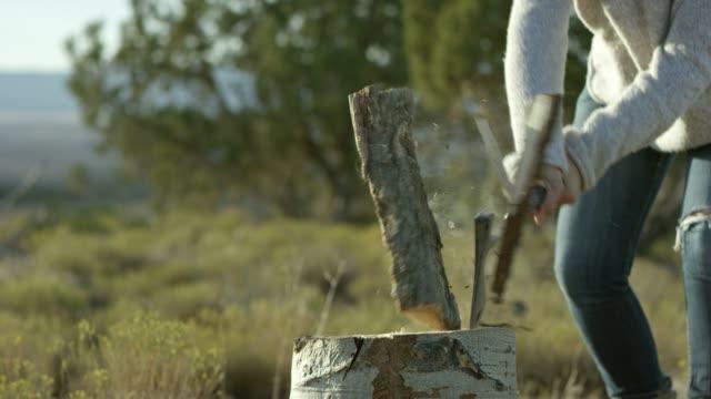 bir kadın bir balta ile odun böler - şömine odunu stok videoları ve detay görüntü çekimi