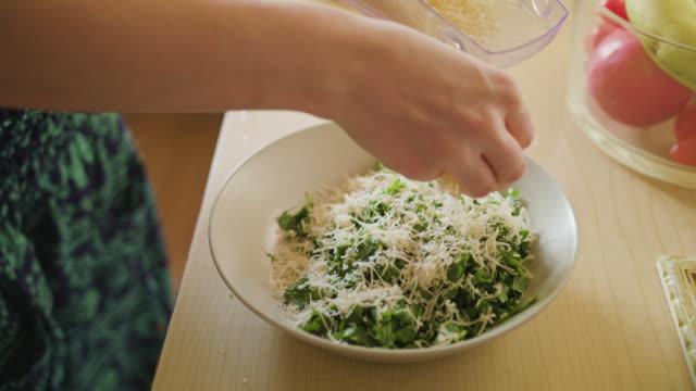 vidéos et rushes de femme sprinkles fromage sur salade - parmesan