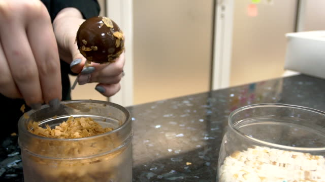 Woman sprinkles chocolate ball with flakes in kitchen indoors