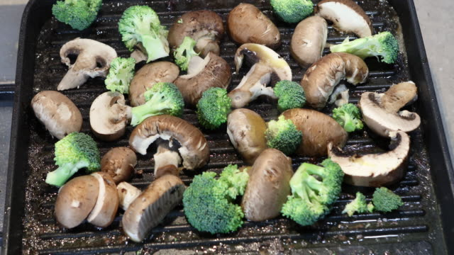 woman sprinkles oil on mushrooms and white mushrooms and broccoli which are fried on a ribbed plate - crucifere brassicali video stock e b–roll