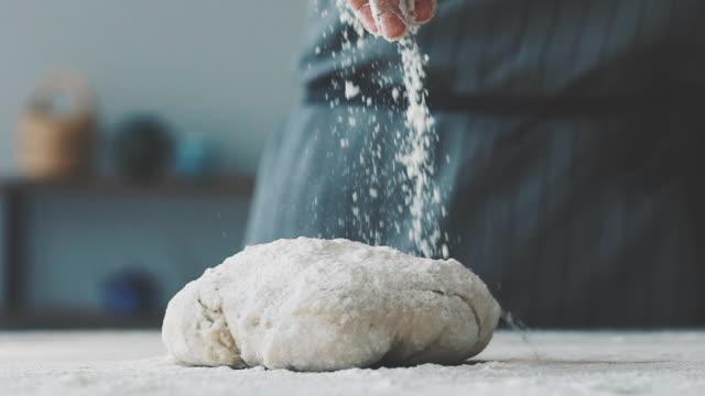 Woman sprinkling flour over dough