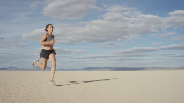 woman sprinting in the desert - biegać filmów i materiałów b-roll