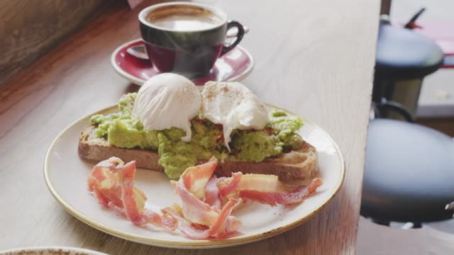 Woman Squeezing Lemon Over Poached Egg And Avocado On Toast video