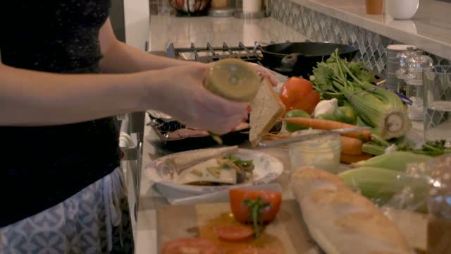 kvinna klämma senap från en plastflaska på en smörgås på en papper plattan - cheese sandwich bildbanksvideor och videomaterial från bakom kulisserna