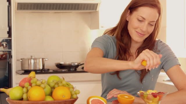Woman squeezing orange over her fruit salad video