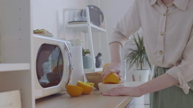 woman squeezing oranges in the kitchen - articoli casalinghi video stock e b–roll