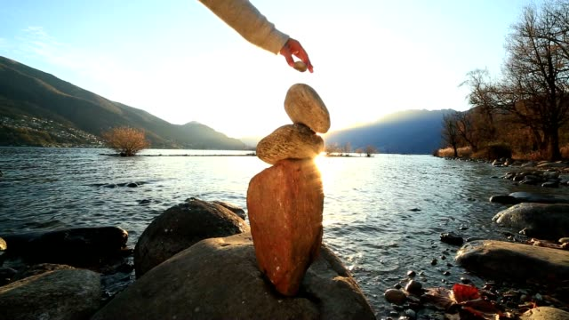 woman stacking rocks by the lake - naturopathy stock videos and b-roll footage