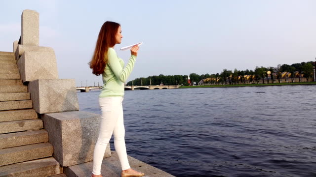 Woman stand on river bank hold paper plane in hand ready to throw, slow motion video