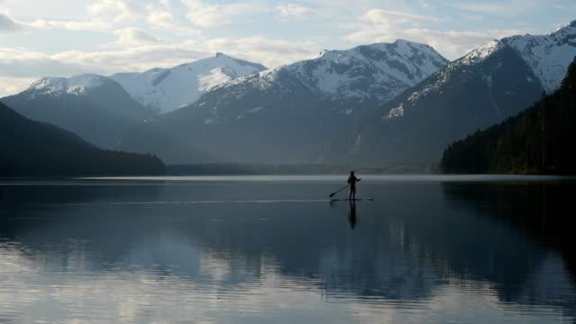 frau stand-up paddle boarding auf einem unberührten bergsee - britisch kolumbien stock-videos und b-roll-filmmaterial