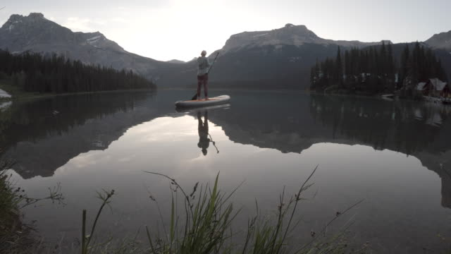 Woman stand up paddleboards across mountain lake  pedal pushers stock videos & royalty-free footage