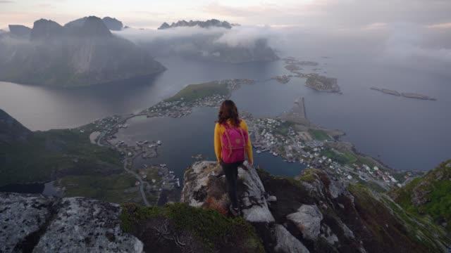 vídeos de stock e filmes b-roll de woman standing and looking from reinebringen mountain on lofoten island - reine