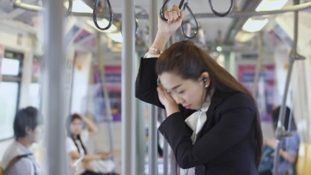 女性は立っていると、電車の中で昼寝します。 - 列車点の映像素材/bロール