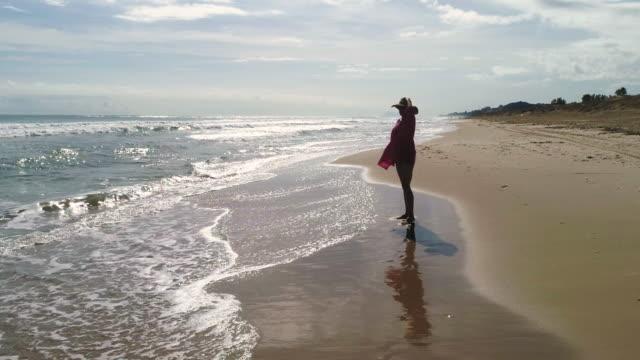 en kvinna som står och stirrar vid horisonten på en gyllene sandstrand och reflektioner - endast unga kvinnor bildbanksvideor och videomaterial från bakom kulisserna