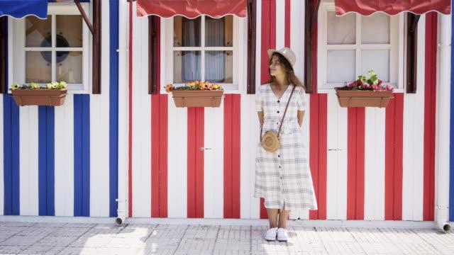 vídeos de stock e filmes b-roll de woman standing at background colored house - aveiro