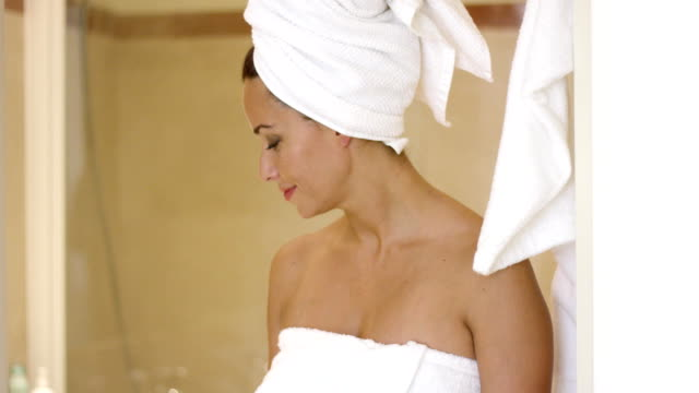 Woman standing at shower stall wrapped in towels Beautiful young adult woman leaning at entrance of shower stall or sauna while wrapped in towels wearing a towel stock videos & royalty-free footage