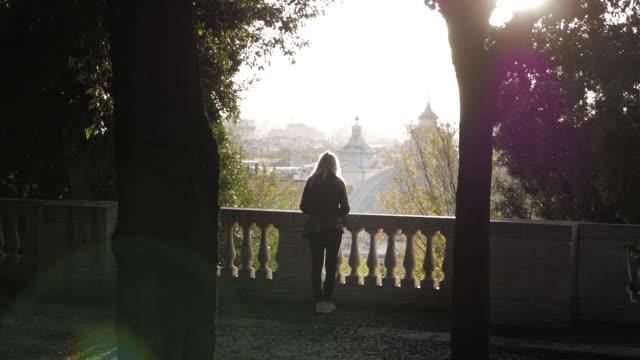woman standing at sunlit balustrade in rome - balaustrata video stock e b–roll