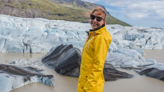 Woman standing at the bottom of glacier Young woman in yellow raincoat standing at the bottom of an Icelandic glacier, admiring it and then turning around and smiling into camera polar climate stock videos & royalty-free footage