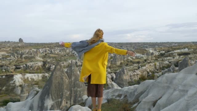 woman standing back enjoying the view of the rocky valley of Cappadocia
