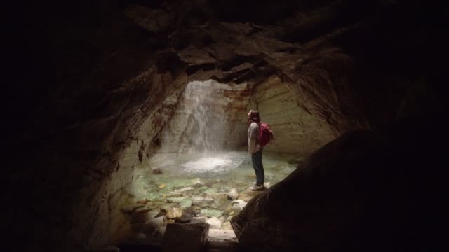 Woman standing in cave and looking at waterfall