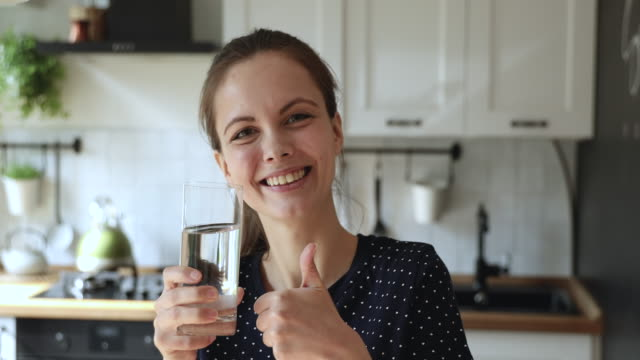 Woman standing in kitchen holding glass of water showing thumbsup