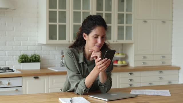 kvinna som står i köket med hjälp av internet på smartphone - e post bildbanksvideor och videomaterial från bakom kulisserna