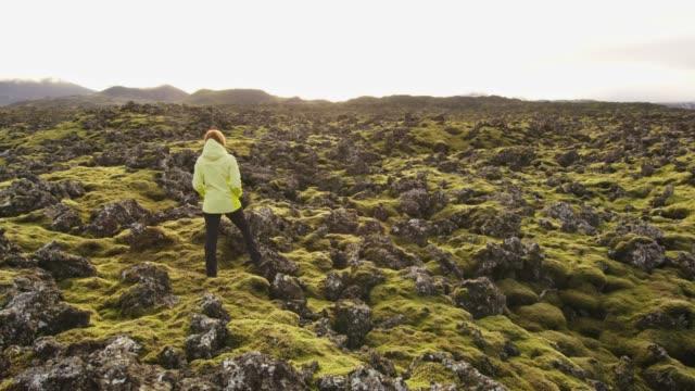 ms woman stående i robust, avlägsen landskap, island - torv bildbanksvideor och videomaterial från bakom kulisserna