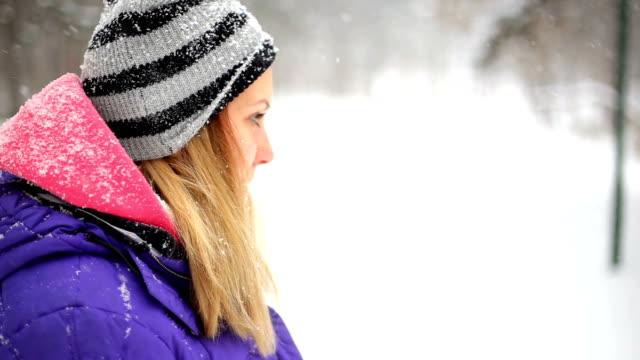 donna in piedi in un campo di neve guarda - abiti pesanti video stock e b–roll