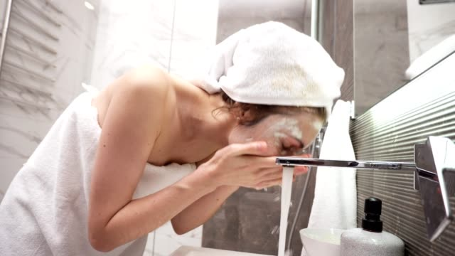 a woman standing in the bathroom near the sink in white towel on head and body washes off a white cosmetic mask with water from the tap. side view - disintossicazione video stock e b–roll