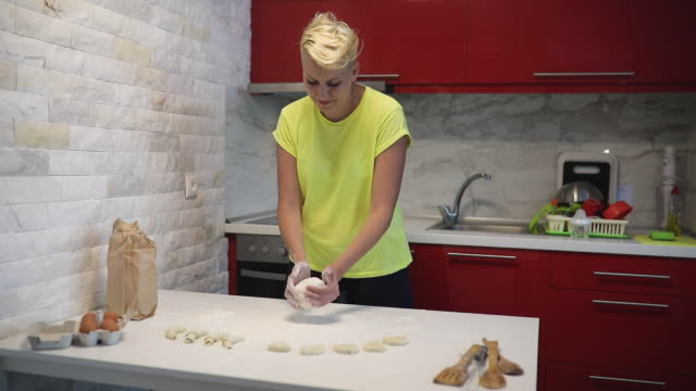 vídeos de stock e filmes b-roll de woman standing in the kitchen by table and kneading dough - baking bread at home