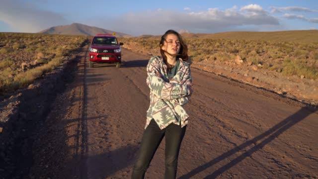 Woman standing near pickup car in   Atacama desert in Chile