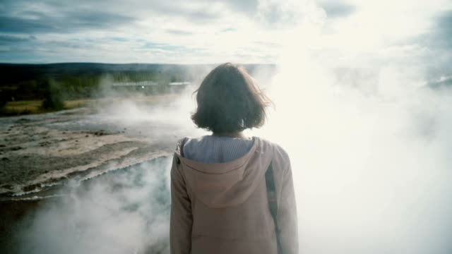 Woman standing near the Geyser in Iceland video