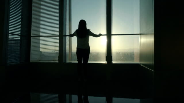 Woman standing near window in office looking out video