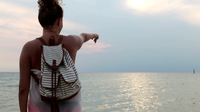 Woman standing on a beach near the water with the backpack and pointing at the horizon video