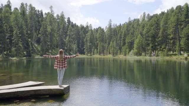 Woman standing on a wooden pier by Alpine lake arms wide open