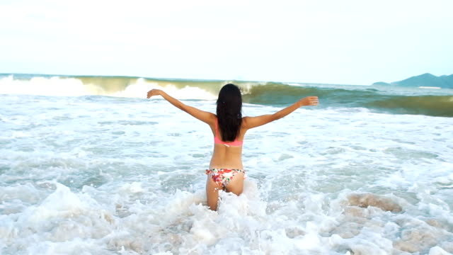 Woman standing on beach in summer. Asian girl going to sea and rising hands up. video