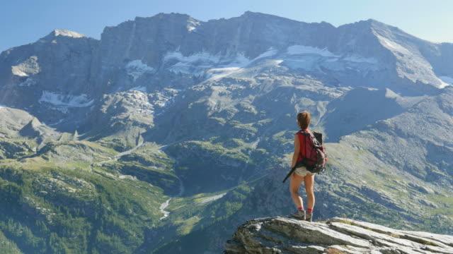 vídeos y material grabado en eventos de stock de mujer de pie en la cima de la montaña en los alpes, cámara lenta - escalada en rocas